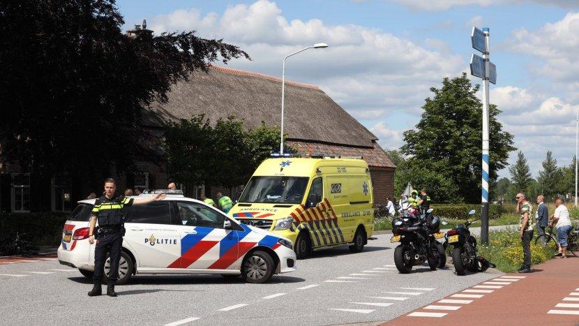 Politie zet de weg af terwijl ambulancepersoneel een slachtoffer verzorgen achter de ambulance