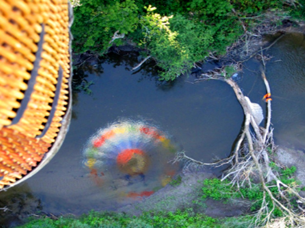 Reflection of a hot air balloon in the river below