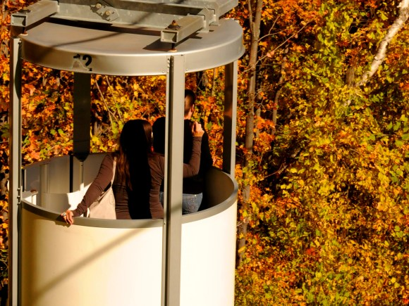 Two women viewing fall colour from an open-air gondola