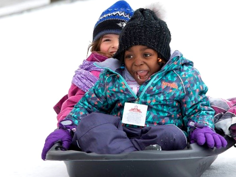 Two little girls tobogganing down a snowy hill.