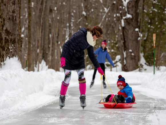 A woman on skates pulling a child on a toboggan
