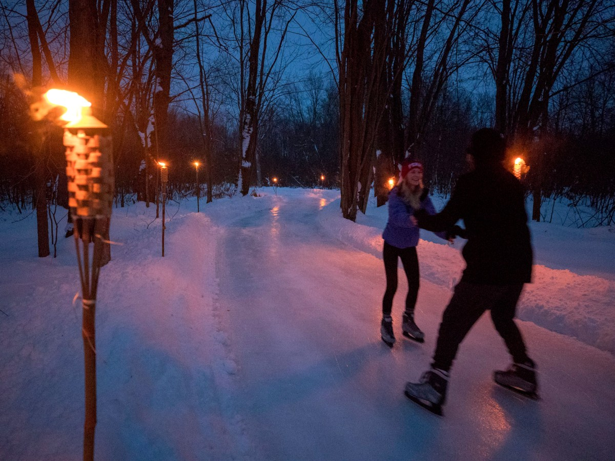 A couple skating by tiki torches at night