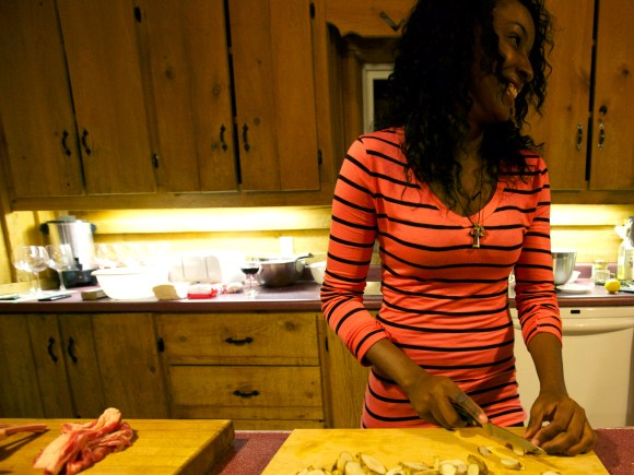 A smiling woman cutting up potatoes in the kitchen