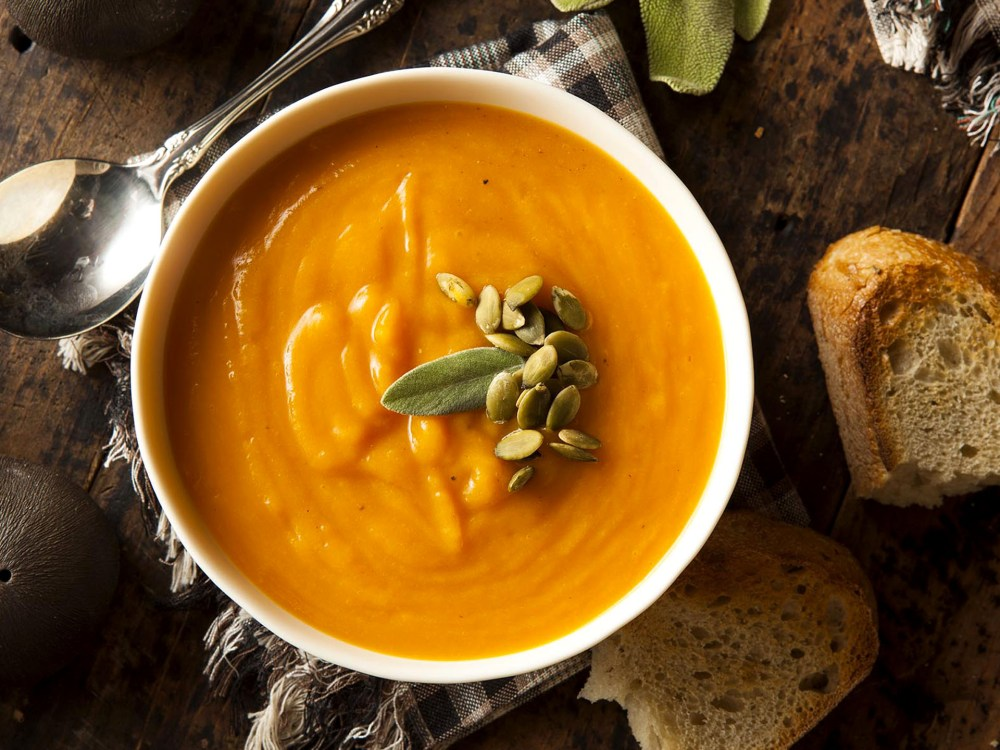 a bowl of pumpkin soup with hearty bread on the side