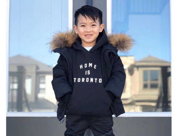 A boy wearing a 'Home is Toronto' sweatshirt