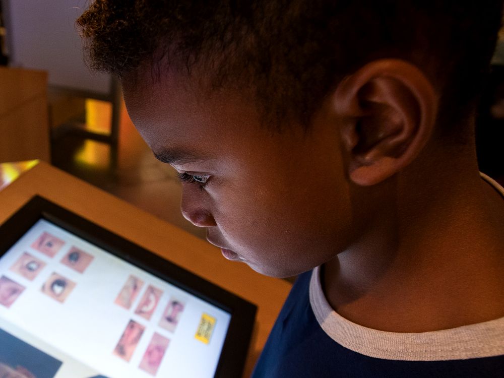 A young boy is engrossed in a digital program from the Ontario Science Centre