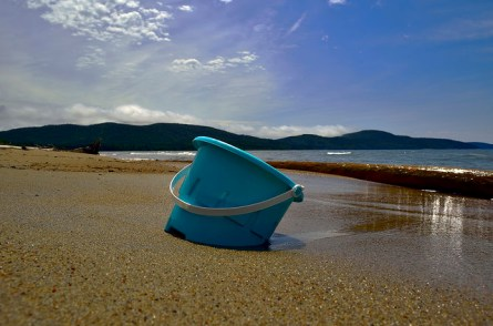 An abandoned toy bucket in the sand.