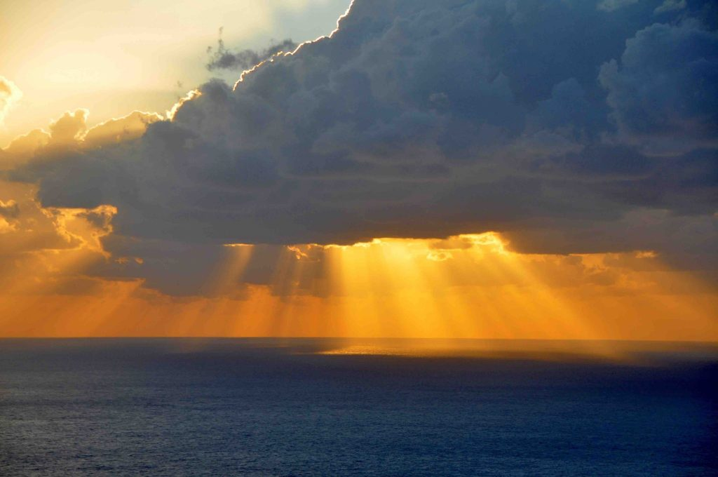 Gouden zonnestralen achter de woklen boven de zee Evia Griekenland