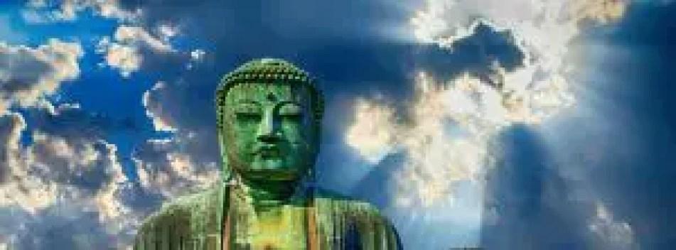 Een groot boeddhabeeld met daarachter de zon die door de wolken breekt