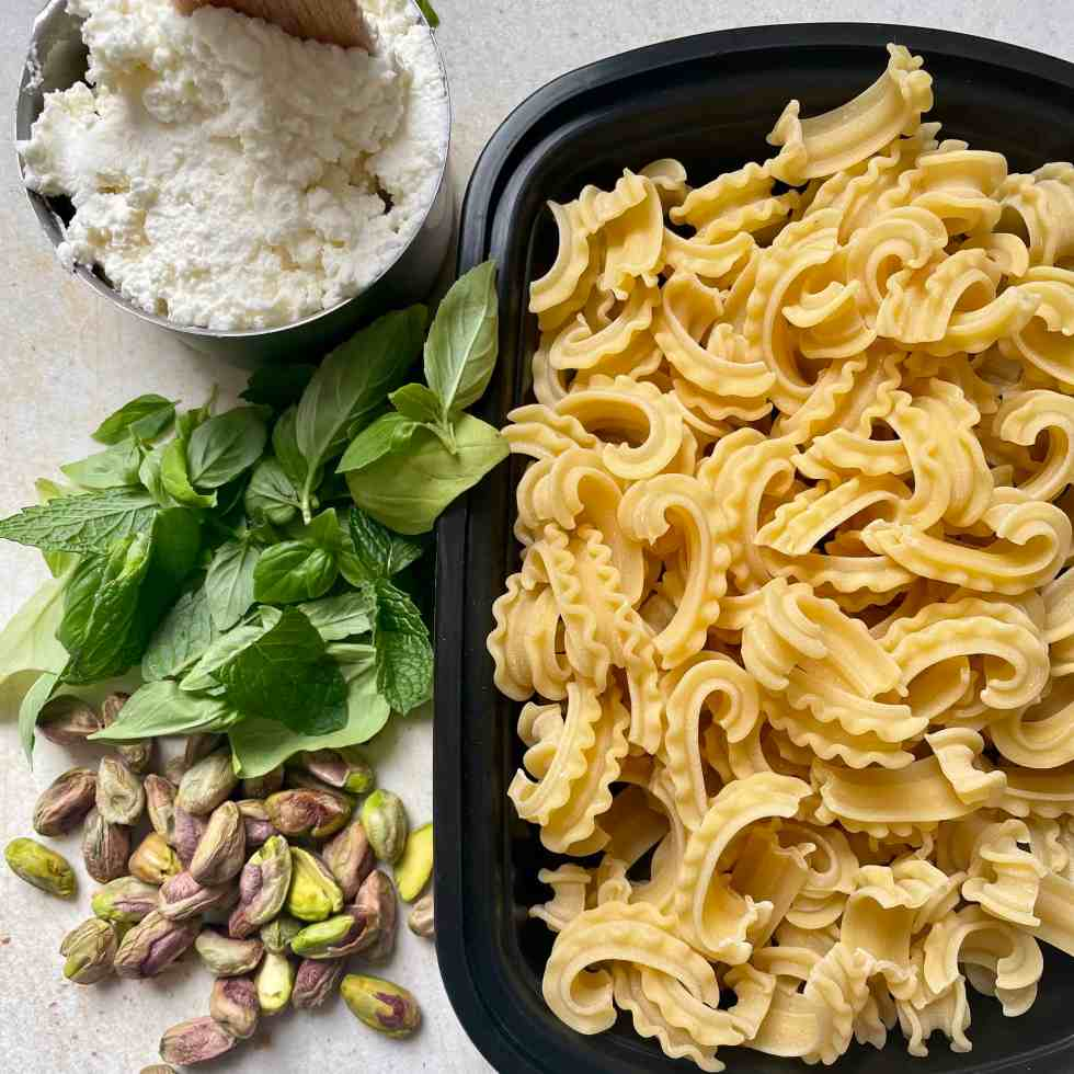 Cutting board containing cascatelli, the new pasta shape, alongside pistachios, mint, basil, and ricotta cheese.