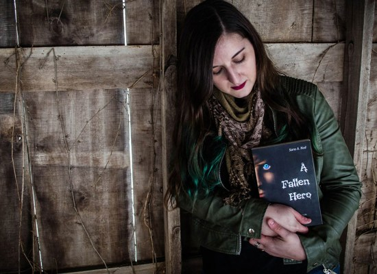 Author Sara A. Noe with her novel Chronicles of Avilesor: War of the Realms book 1, A Fallen Hero in front of a rustic wooden background