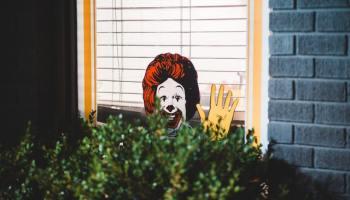 McDonald's Mascot is Partially Hidden by a Bush