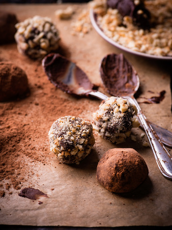 assorted dark chocolate truffles with cocoa powder, biscuit and chopped hazelnuts over baking p