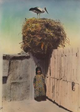 Eric Keast Burke (c.1917) Girl stands for good luck under a stork's nest.