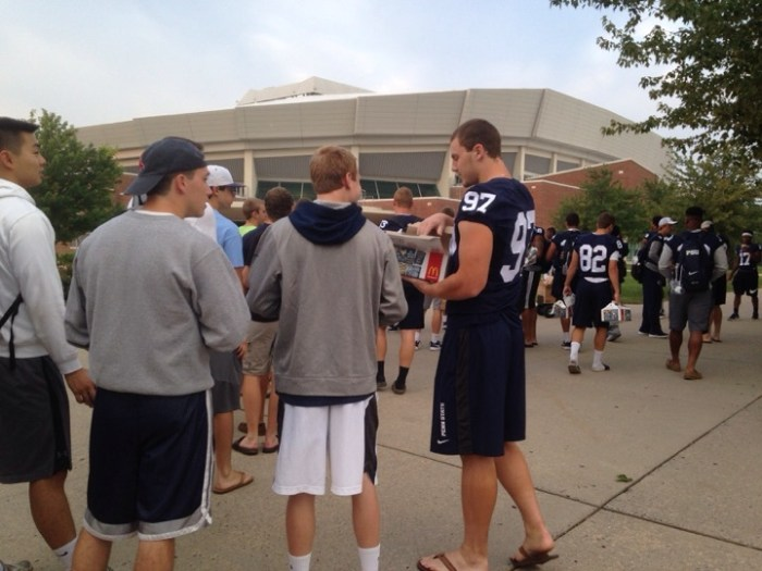 football players handing out food in line