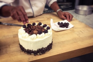 Chef is placing the cherries on top of each rosette.
