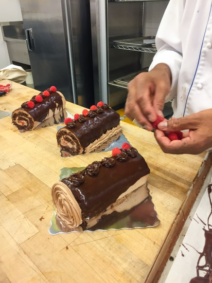 Chef is placing the raspberry on one side of each rosette.