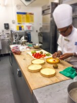 Chef is arrange a variety of fruit in an artistic design covering all cream.