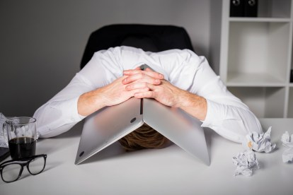 Man hiding under laptop