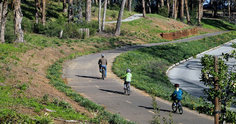 A man and two children cycle along a tree-lined bicycle path in San Mateo County