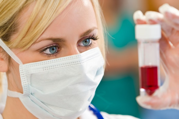 A young female doctor/nurse looking at a blood sample with other medical staff out of focus in the background