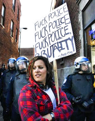 The right message, well stated, merits repetition. (A woman stands near police massed in an alley near the Mont Royal metro station Sunday, March 15, 2009 in Montreal during the annual march against police brutality. John Kenney)