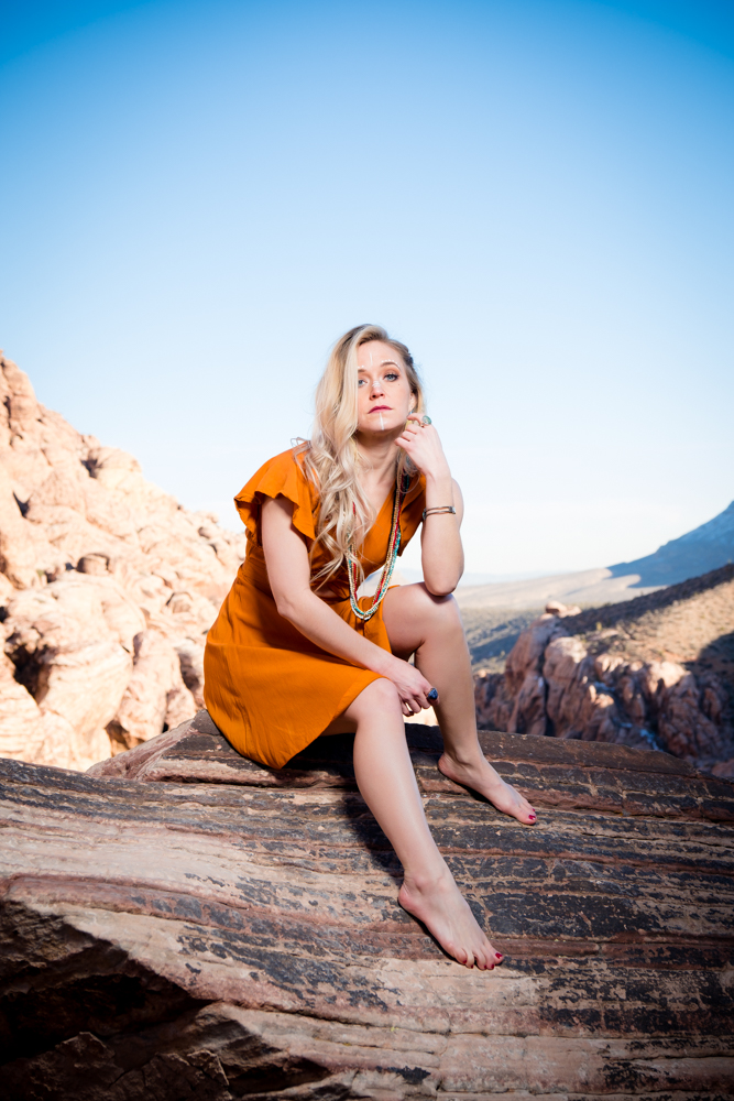 Beautiful woman sitting on a rock edge with a mountain in the background