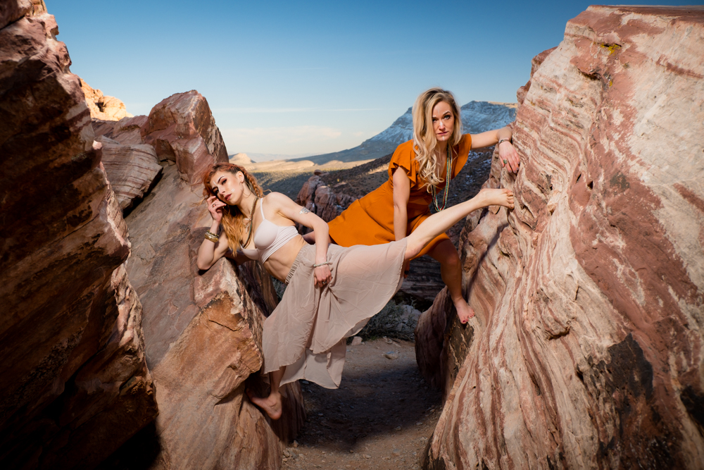 Two gorgeous dancers posing casually while holding themselves up ebtween two large rocks