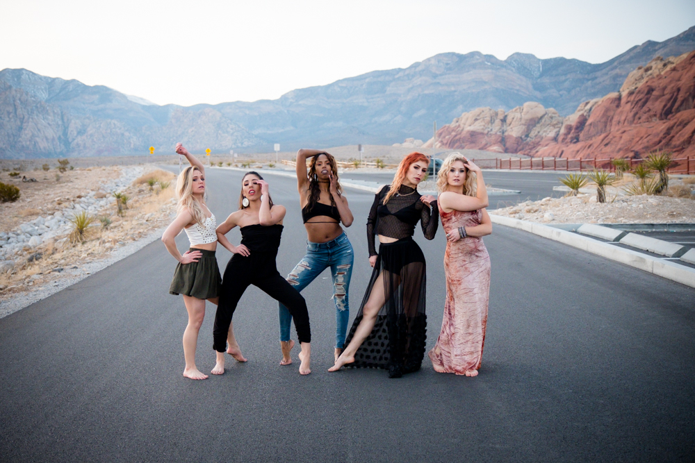 Vegas Bombshells dance crew striking a pose in the middle of a desert road