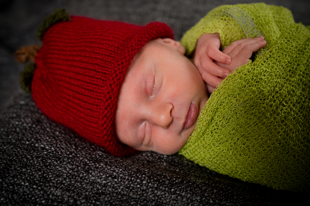 Newborn baby boy wrapped in green with a red apple hat