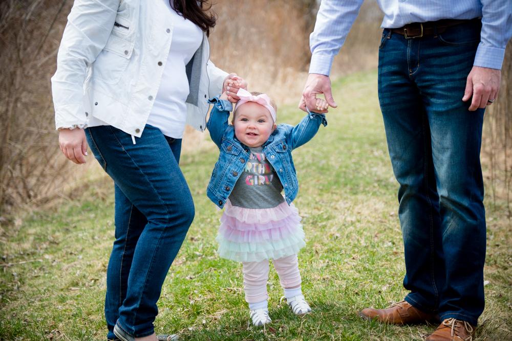Baby girl standing between her parents