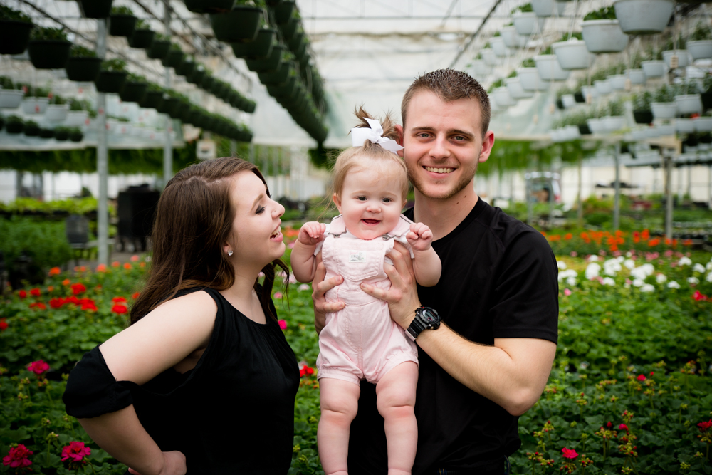 Family of 3 smiling in a greenhouse