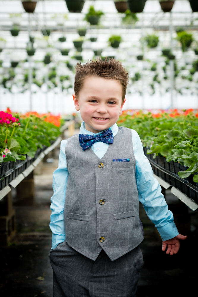 Little boy posing cute in a greenhouse