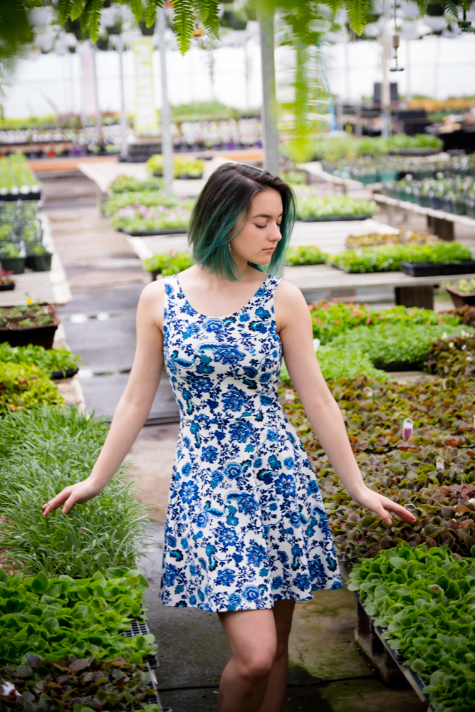 Teenager in blue walking in a greenhouse