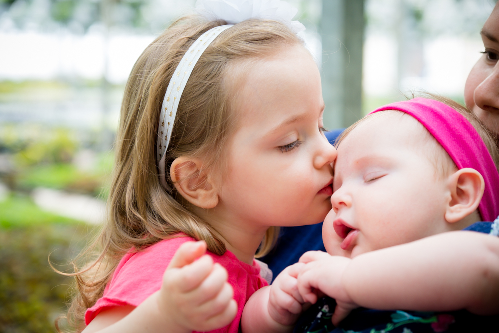 Little girl kissing her sister