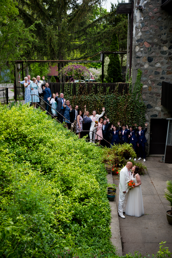All wedding attendees on stone stairs cheering with bride and groom kissing