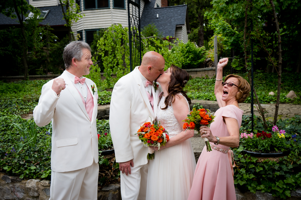 Bride and groom kissing while maid of honor and best man cheer enthusiastically