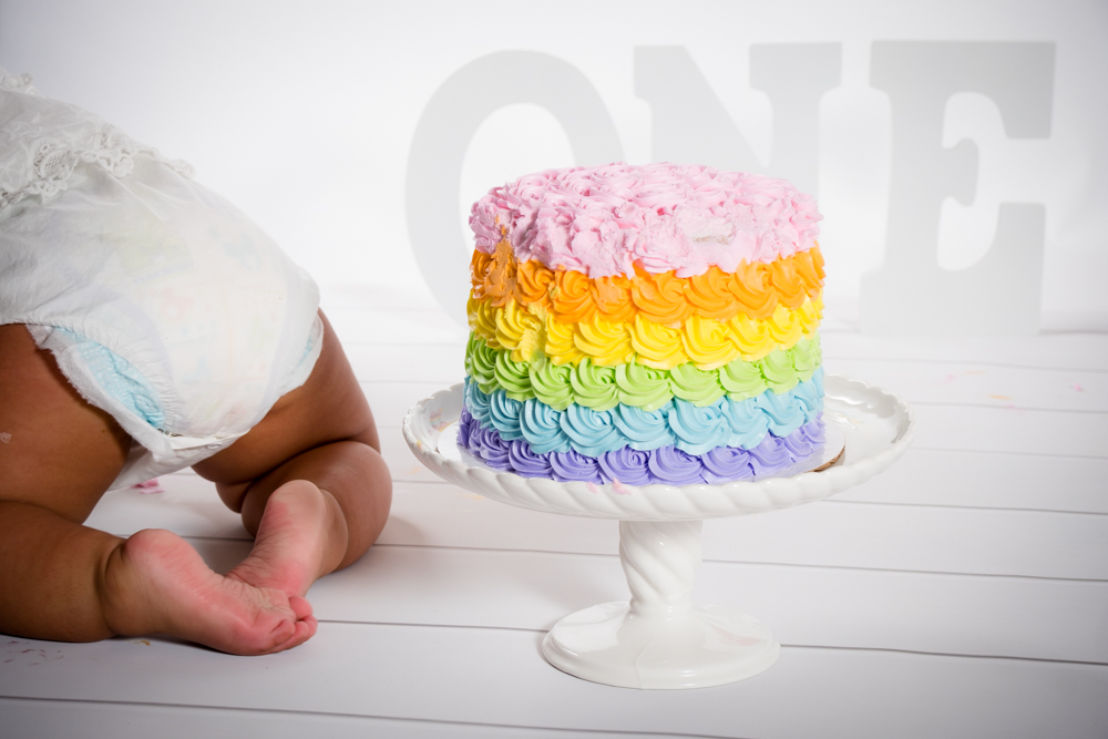 Rainbow birthday cake a a baby's bottom crawling away from it.