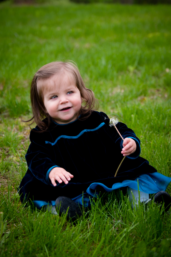 smiling baby girl sitting in the grass