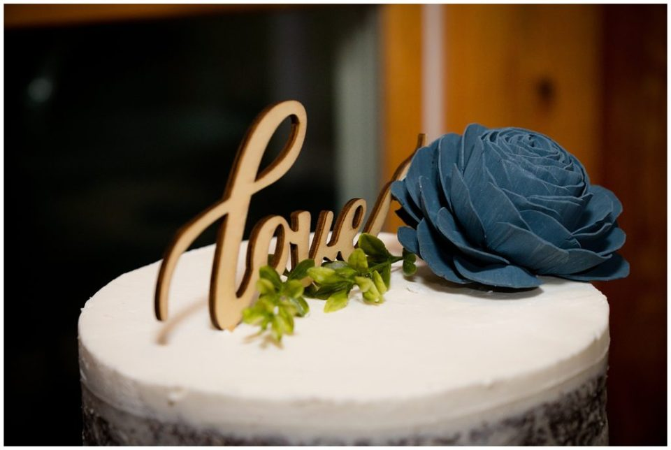 "The word ""love"" carved out of wood as a cake topper for the wedding cake."