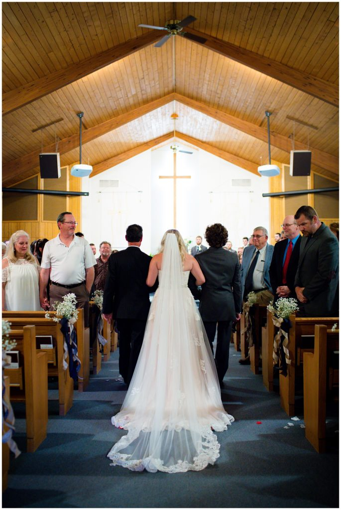 Bride walking down the aisle with her father and brother.