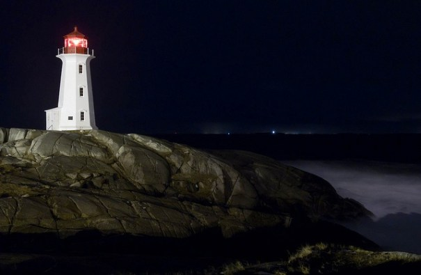 A lighthouse watches over dark water at night.
