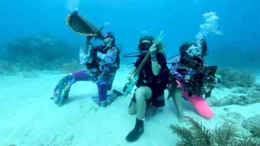 Three people underwater wearing snorkeling equipment and playing instruments