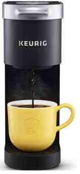 keurig coffee maker with coffee being poured into a yellow mug