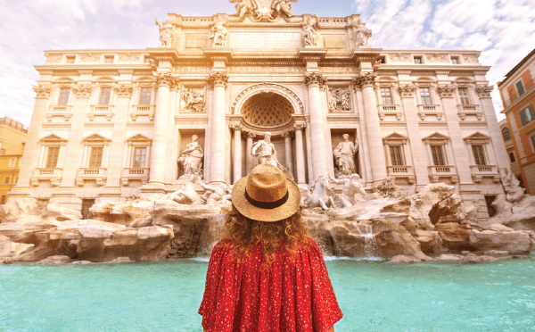 Woman standing in front of the trevi fountain