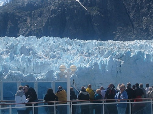 People on cruise ship deck in front of a glacier in Alaska
