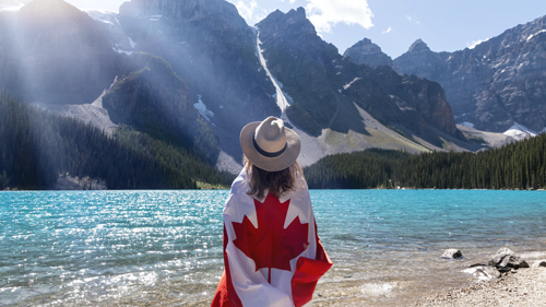 A person wrapped in a Canadian flag looking out at Moraine Lake in Banff National Park.