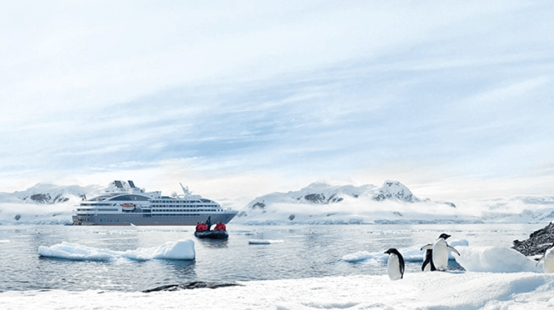 Ponant cruise ship in Antarctica with glaciers and penguins