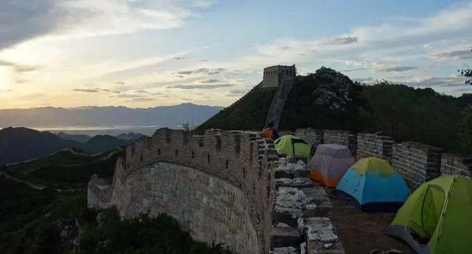 Alcuni viaggiatori dormono in tenda lungo la Grande Muraglia Cinese. Photo Credits.