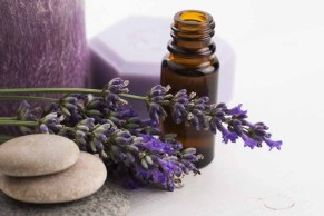 essential-oil-bottle-with-lavender-candle-and-stones